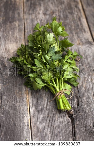 Organic celery on a rustic wooden board - stock photo