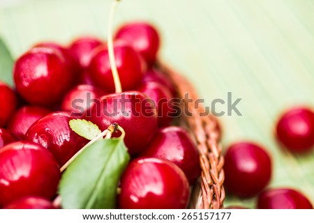 Organic Cherries in a Basket on a green background - stock photo