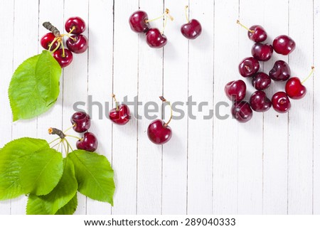 organic cherry fruits on white wooden table background - stock photo