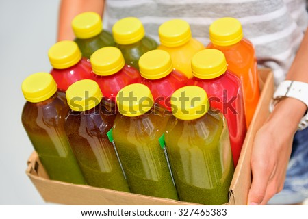 Organic cold-pressed raw vegetable juice plastic bottles. Latest food trend consisting of juicing at high pressure fresh fruits and vegetables without heating to preserve nutrients and vitamins. - stock photo