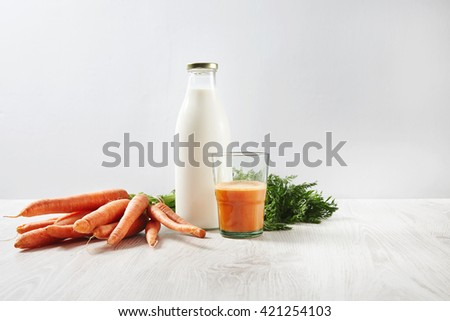 Organic farm carrot harvest lying near bottle with milk and glass half filled with natural fresh juice for breakfast. Isolated on white background on wooden table in cafe shop - stock photo