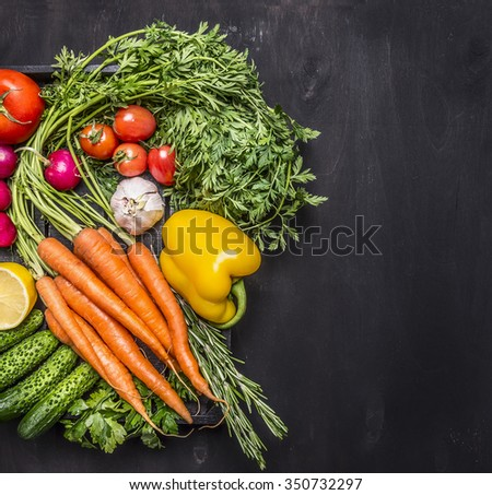 organic farm vegetables fresh carrots cherry tomatoes, garlic, cucumber, lemon, pepper, radish, wooden spoon salt and pepper colored, oil wooden rustic background top view border, place for text  - stock photo