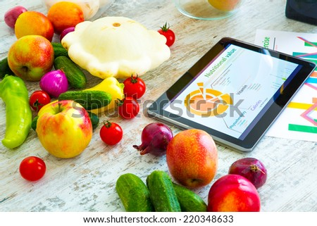 Organic food and a Tablet PC showing information about healthy nutrition and phytochemical composition. - stock photo
