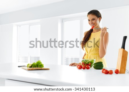 Organic Food. Portrait Of Young Smiling Woman Eating Fresh Healthy Vegetable Salad In Modern Kitchen. Healthy Eating, Meal, Lifestyle Concept. Health, Diet, Fitness. Nutrition. - stock photo