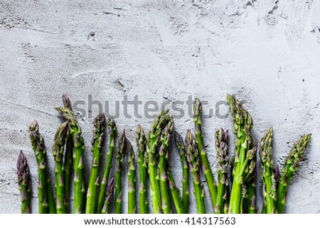 Organic fresh asparagus over concrete textured background, top view, space for text. - stock photo