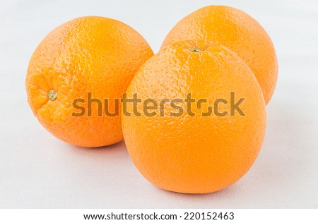Organic Fresh juicy navel oranges on tablecloth white background - stock photo