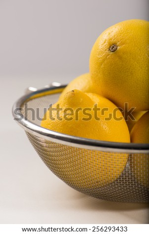 organic, fresh lemons in a metal strainer over a white background with copy space, close up, vertical. - stock photo