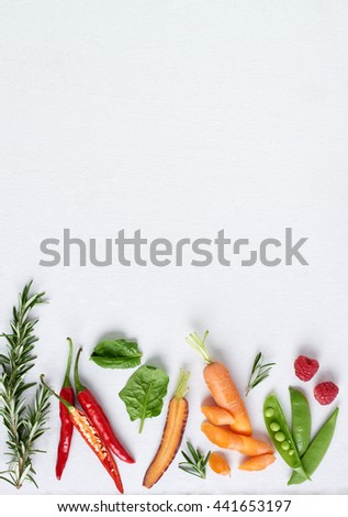 Organic fruit and vegetables herbs on white background, rosemary, chilli, spinach, heirloom carrots, raspberry, plenty of copy space - stock photo