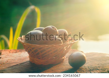 Organic fruits in basket on wooden background. Vintage retro composition - stock photo