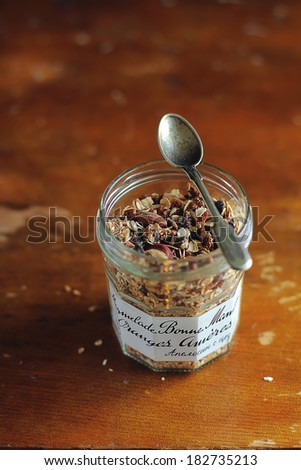 Organic granola with toasted oats, roasted hazelnuts, dates, raisin and dried figs in a jar for healthy breakfast or snack - stock photo