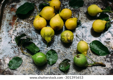 organic green and yellow pears from farmers market on aged background rustic style natural light overhead shot - stock photo