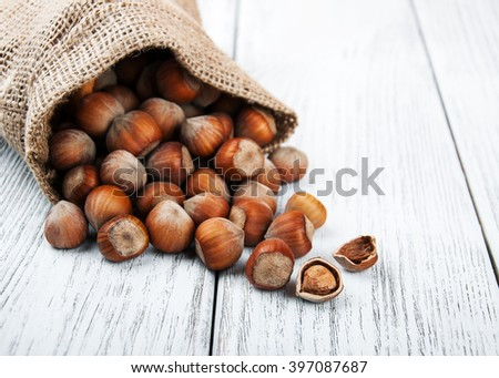 organic hazelnuts in bag on a old wooden table - stock photo