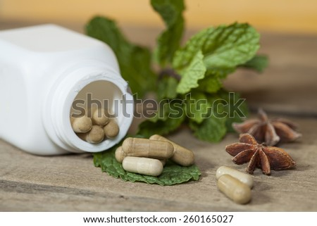 Organic Herb capsule medicine with mint leaves - stock photo