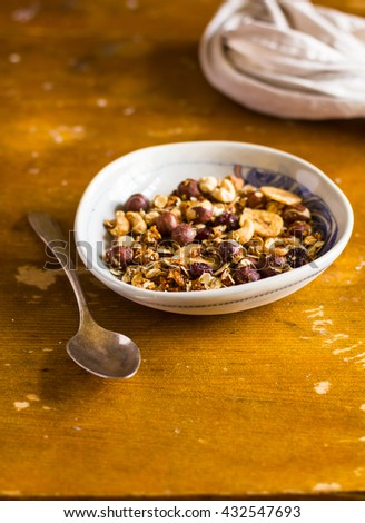 Organic homemade granola or muesli bowl with dried cranberry, figs, banana chips, hazelnuts and cashew in a bowl on a wooden table, selective focus - stock photo