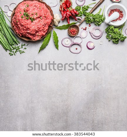 Organic Minced Meat with cooking ingredients , wooden spoon and spices mortar  on gray stone background, top view, place for text. Meat food - stock photo