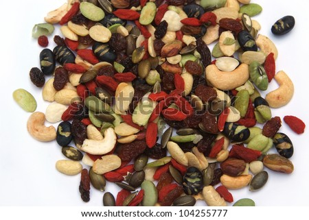organic mixed nuts and dry fruits on white background - stock photo