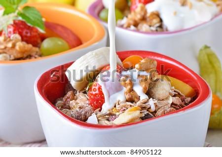 Organic muesli with fresh fruit and milk - stock photo
