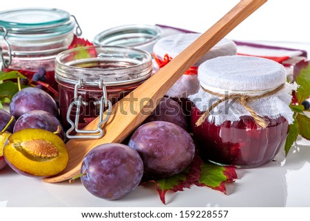 Organic plums and fresh homemade jam on white background - stock photo
