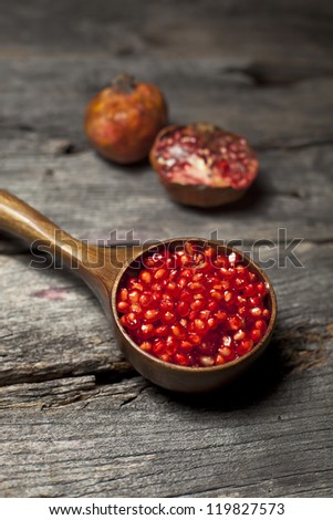 Organic pomegranate and pomegranate seeds on a rustic wooden board - stock photo