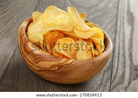 organic potato chips in bowl on wood table - stock photo