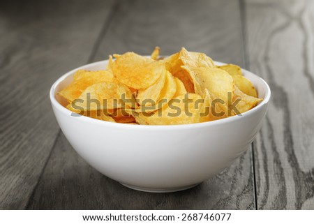 organic potato chips in white bowl on wood table - stock photo