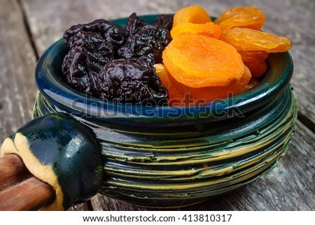 Organic prunes, dried plums and dried apricots in old tableware on rustic table - stock photo