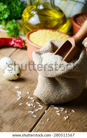 Organic rice grains in burlap sack on kitchen table with food ingredients - stock photo