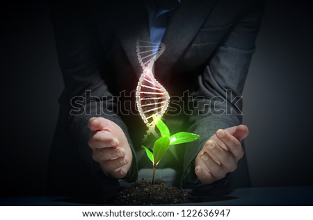 Organic Science theme with DNA and young green sprout rising - stock photo