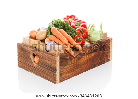 Organic seasonal vegetable in rustic wooden crate isolated on white background. Healthy vegetable eating.  - stock photo
