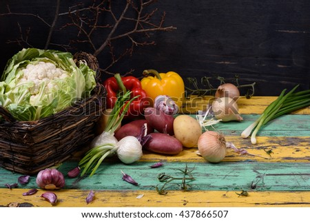 Organic seasonal vegetable ingredients over colorful wooden table. Healthy food or vegetarian diet concept. - stock photo