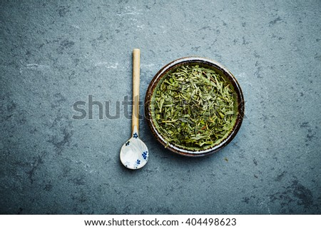 Organic Sencha green tea with ceramic spoon on a stone background - stock photo