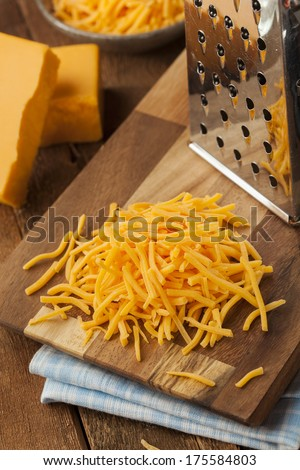 Organic Shredded Sharp Cheddar Cheese on a Cutting Board - stock photo