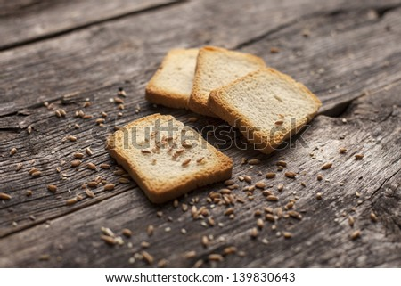 Organic toast bread on a rustic wooden board - stock photo