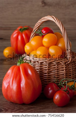 Organic tomatoes in wicker basket on a garden wooden table. - stock photo