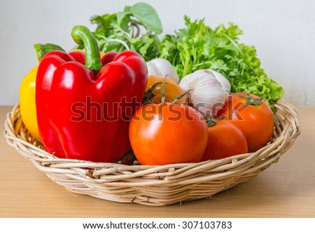 Organic vegetables in the wicker basket on wooden background - stock photo