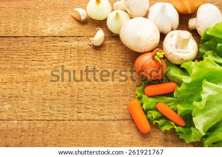 Organic vegetables on a wood background. Onion, parsley, champignons on a burlap - stock photo