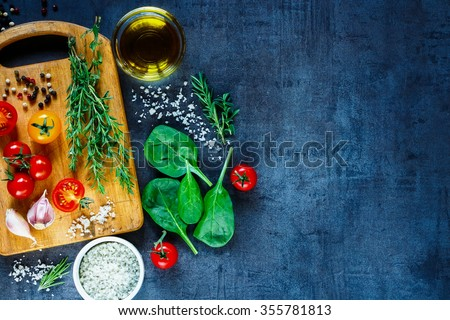 Organic vegetarian ingredients, olive oil and seasoning on rustic wooden cutting board over dark vintage background with space for text, top view. Healthy food, vegan or diet nutrition concept. - stock photo