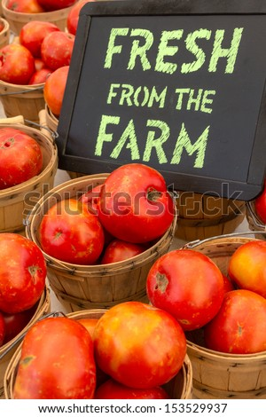 Organically grown red tomatoes in baskets for sale at local farmer market with chalkboard sign - stock photo