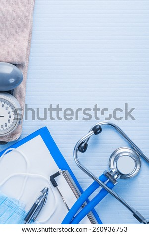 organized copyspace clipboard with white blank paper masks pen stethoscope blood pressure monitor on blue background medical concept  - stock photo