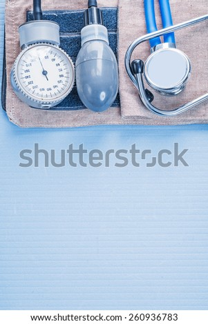 organized copyspace stethoscope with blood pressure monitor on blue background medical concept  - stock photo