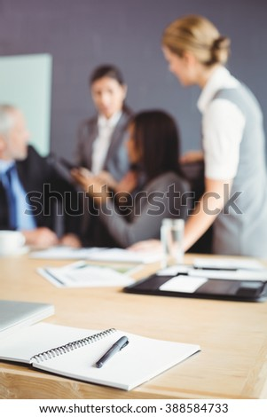 Organizer with pen on table in conference room and businesspeople interacting in background - stock photo
