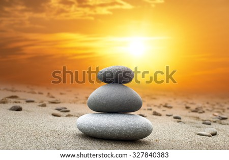 Oriental background of stones pyramid at sunset with bright yellow sun on evening sky - stock photo
