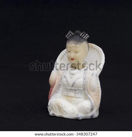 Oriental beauty - antique figurine from bone. Background is black. - stock photo