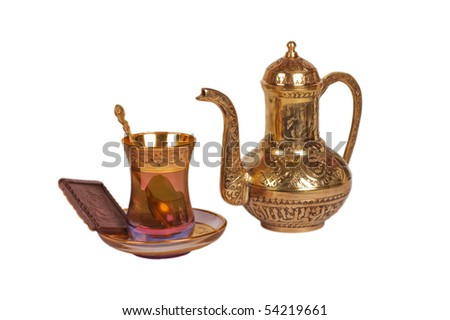 Oriental cup with tea, spoon and kettle - stock photo