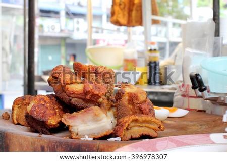 Oriental Roast Pork Belly on wooden chopping board with market women - stock photo