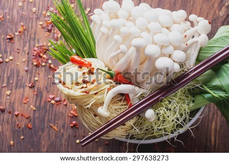 Oriental style lunch preparation: shimeji mushrooms, red chili pepper, bok choi, moyashi springs and mi trung egg noodles in vintage japanese bowl on the rustic wooden board - stock photo