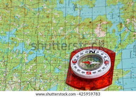 Orienteering using a map and compass. Magnetic compass on a topographic map. - stock photo