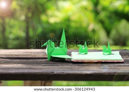 Origami Bird on Handmade notebook, on green background - stock photo