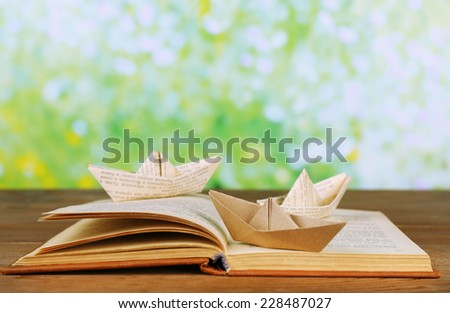 Origami boats on old book on wooden table,  outdoors - stock photo