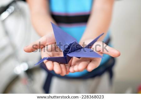 Origami crane in children's hands (soft focused) - stock photo